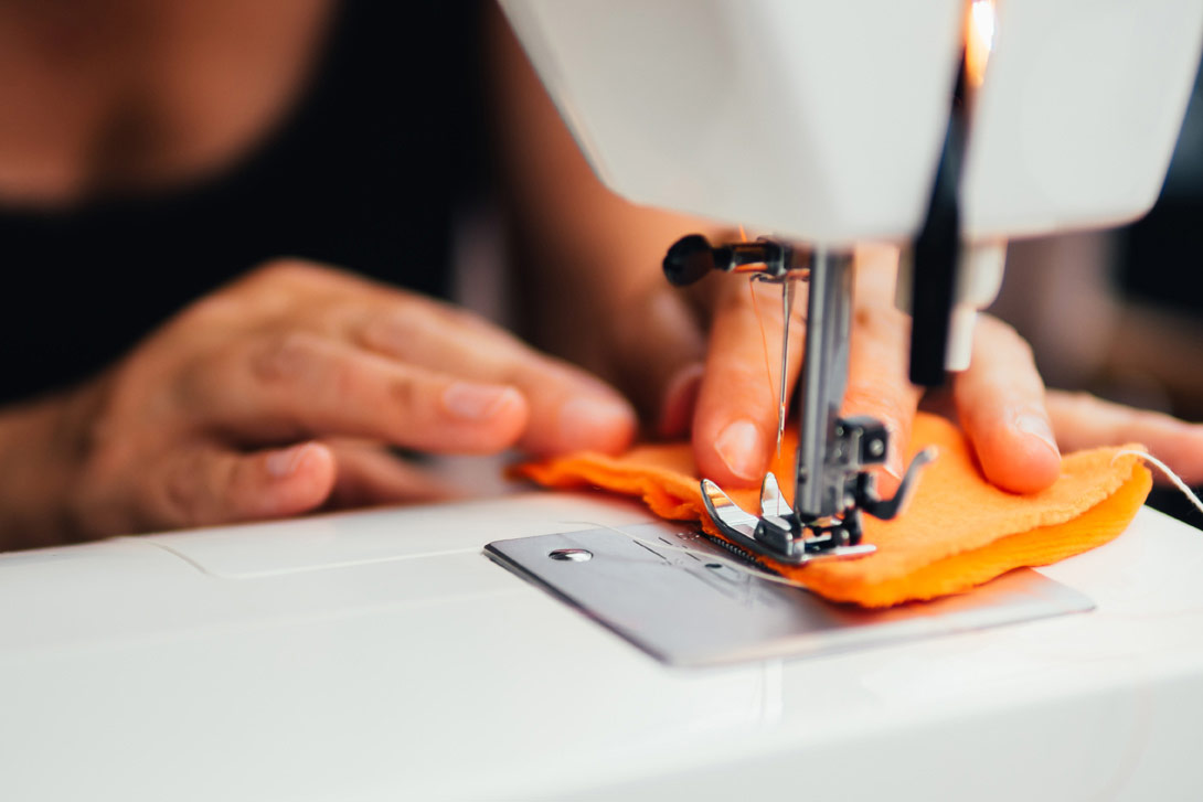 a woman sewing an orange cloth with a sewing machine