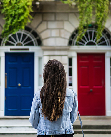 A woman facing a blue door and a red door